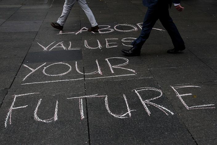 <p>Morning commuters walk past a Labor message on the ground during a Medicare Rally at Martin Place on July 1, 2016 in Sydney, Australia. Bill Shorten is campaigning heavily on Medicare, promising to make sure it isn't privatised if the Labor Party wins the Federal Election on July 2. (Photo by Lisa Maree Williams/Getty Images) </p>