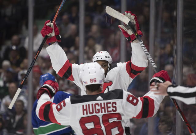 New Jersey Devils' Wayne Simmonds, back, and Jack Hughes (86) celebrate Simmonds' goal against the Vancouver Canucks during the first period of an NHL hockey game in Vancouver, British Columbia, Sunday, Nov. 10, 2019. (Darryl Dyck/The Canadian Press via AP)