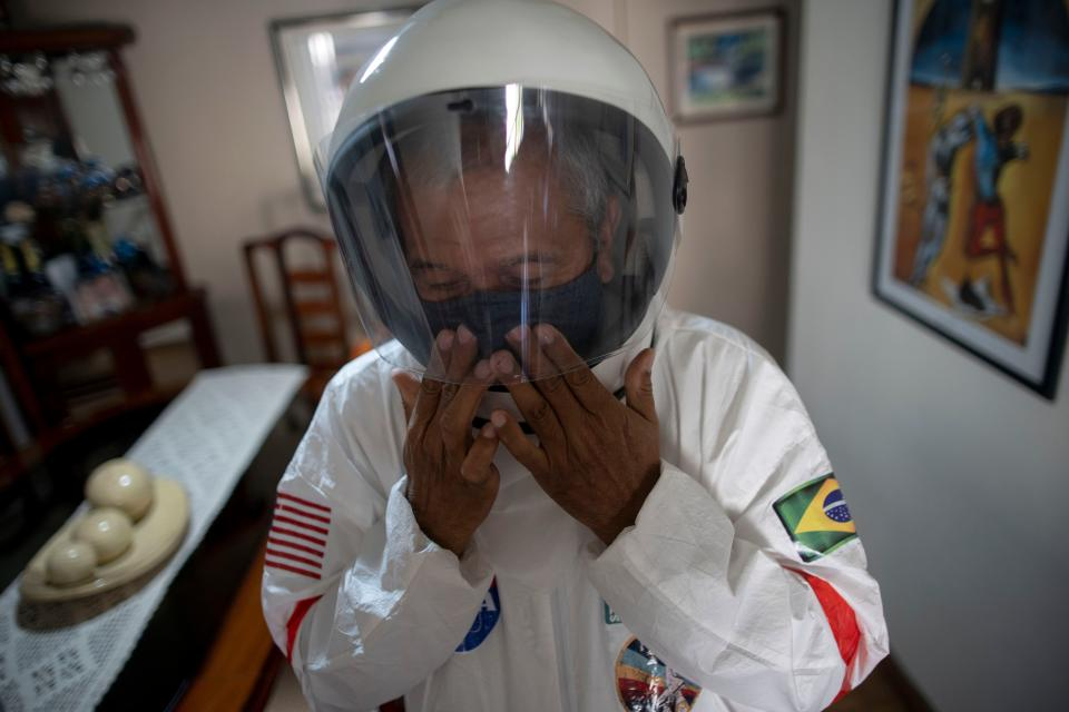 TOPSHOT - Brazilian accountant Tercio Galdino, 66, puts a helmet on as he prepares to go to Copacabana beach in protective suit, in Rio de Janeiro, Brazil on July 12, 2020. - Tercio, who has a chronic lung disease, made protective suits (looking like astronauts gear) for him and his wife at home using suits used by health professionals. He says that, in addition to giving him protection against the new coronavirus, they also wear them for fun, as he has huge interest in astronomy. (Photo by Mauro Pimentel / AFP) (Photo by MAURO PIMENTEL/AFP via Getty Images)