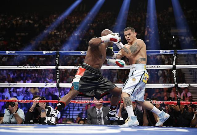 Floyd Mayweather Jr., left, trades blows with Marcos Maidana, from Argentina, in their WBC-WBA welterweight title boxing fight Saturday, May 3, 2014, in Las Vegas. (AP Photo/Eric Jamison)
