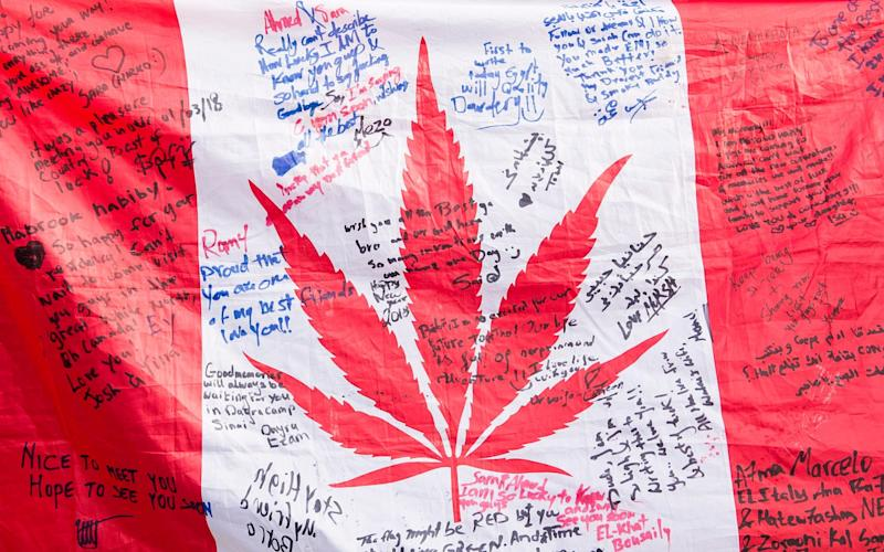 People hold up a Canadian flag with a marijuana logo on it outside a government cannabis store in Montreal - The Canadian Press