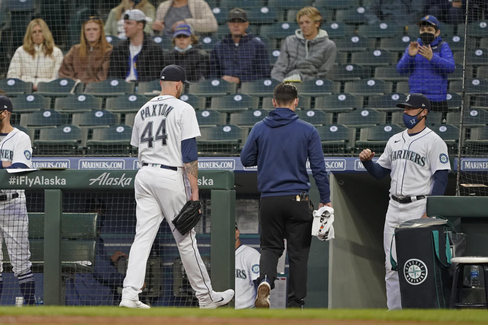 Fans watch as Seattle Mariners starting pitcher James Paxton (44) heads to the clubhouse with a trainer during the second inning of the team's baseball game against the Chicago White Sox, Tuesday, April 6, 2021, in Seattle. Paxton was replaced by Nick Margevicius. (AP Photo/Ted S. Warren)