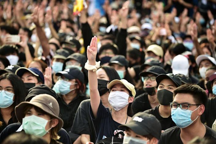 """A protester holds up a three-finger salute at a rally in Bangkok on Aug. 16, 2020. <span class=""""copyright"""">LILLIAN SUWANRUMPHA—AFP/Getty Images</span>"""