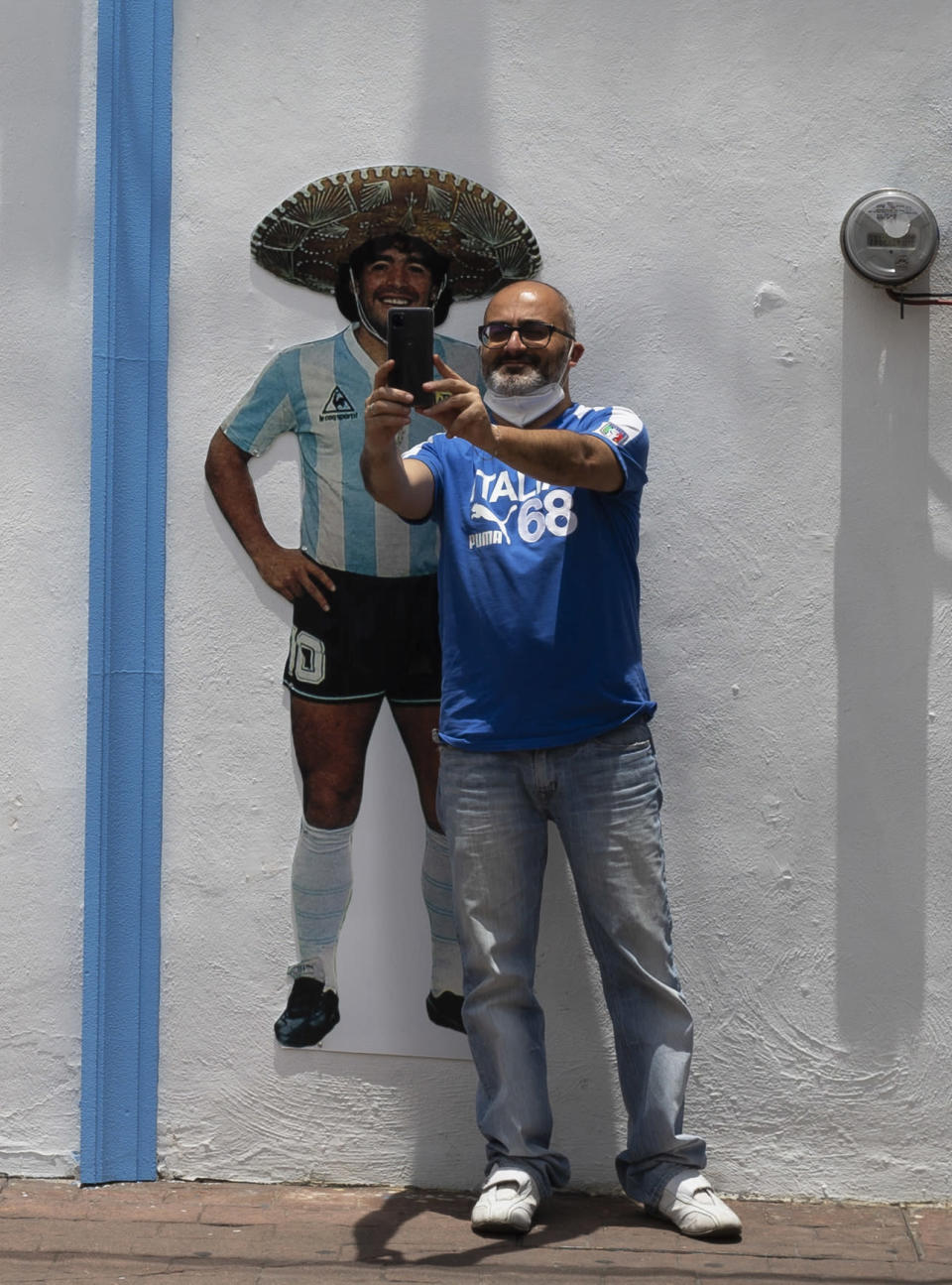 A tourist takes a selfie in front of the Church of Maradona in San Andres Cholula, Puebla state, Mexico, Sunday, July 18, 2021. The Church of Maradona in Mexico, dedicated to late soccer great Diego Armando Maradona, was founded a few weeks ago by Argentine expatriate Buchet, who also owns the pizza parlor next door. (AP Photo/Marco Ugarte)