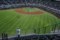A fan watches batting practice from center field before Game 1 of the baseball World Series between the Los Angeles Dodgers and the Tampa Bay Rays Tuesday, Oct. 20, 2020, in Arlington, Texas.(AP Photo/Sue Ogrocki)
