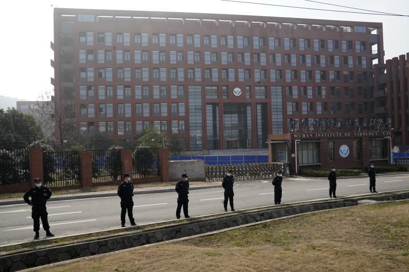 Security personnel gather near the entrance to the Wuhan Institute of Virology during a visit by the World Health Organization team in Wuhan in China's Hubei province on Wednesday, Feb. 3, 2021. The WHO team is investigating the origins of the coronavirus pandemic has visited two disease control centers in the province. (AP Photo/Ng Han Guan)