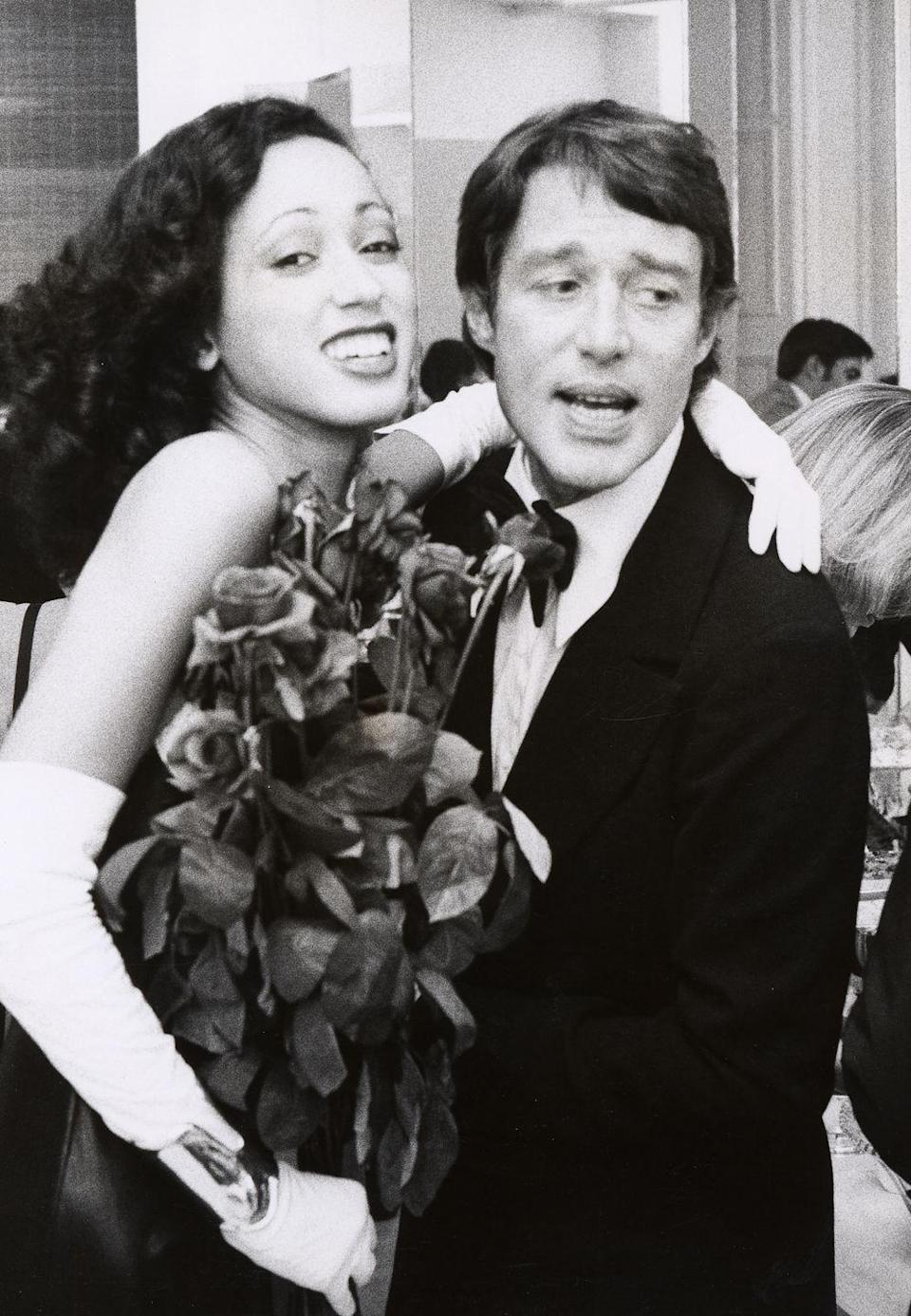 """<p>The designer was known for being close with his models, or """"his girls."""" Model Pat Cleveland was a mainstay in Halston's shows. The two are shown here at a party in his studio.</p>"""