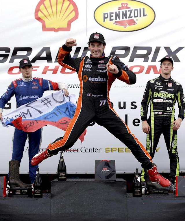 10ThingstoSeeSports - Simon Pagenaud (77), of France, leaps as he celebrates his victory on the winner's stage after the second IndyCar Grand Prix of Houston auto race Sunday, June 29, 2014, in Houston. Joining him on stage are second place finisher Mikhail Aleshin, left, of Russia, and third place finisher Jack Hawksworth, right, of England. (AP Photo/David J. Phillip, File)
