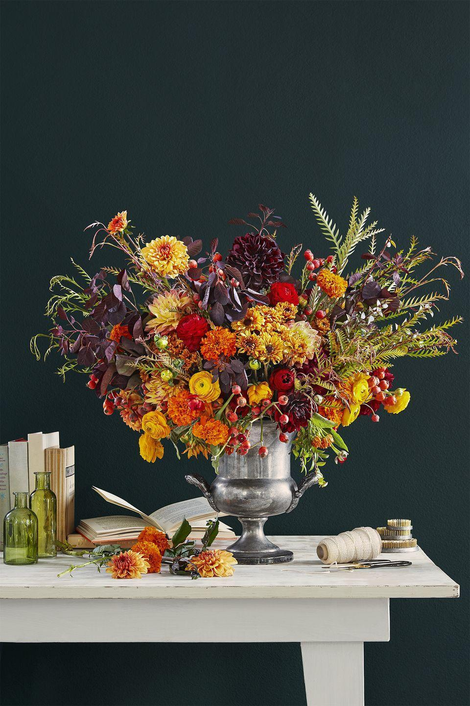 """<p>Bring some autumnal beauty indoors with this arrangement inspired by the yellow, orange, red, and purple leaves on the trees. A vintage trophy (with a <a href=""""https://www.amazon.com/JapanBargain-Japanese-Ikebana-Kenzan-Flower/dp/B0149HTLAO/?tag=syn-yahoo-20&ascsubtag=%5Bartid%7C10050.g.2130%5Bsrc%7Cyahoo-us"""" rel=""""nofollow noopener"""" target=""""_blank"""" data-ylk=""""slk:flower frog"""" class=""""link rapid-noclick-resp"""">flower frog</a> inside) makes the perfect vessel for a big bunch of blooms.</p><p><a class=""""link rapid-noclick-resp"""" href=""""https://go.redirectingat.com?id=74968X1596630&url=https%3A%2F%2Fwww.ebay.com%2Fsch%2Fi.html%3F_from%3DR40%26_trksid%3Dp2334524.m570.l1313.TR11.TRC2.A0.H0.Xvintage%2BTROPHIES.TRS1%26_nkw%3Dvintage%2BTROPHIES%26_sacat%3D0%26LH_TitleDesc%3D0%26LH_TitleDesc%3D0%26_osacat%3D0%26_odkw%3Dvintage%2Bjug%2Bcoolers&sref=https%3A%2F%2Fwww.countryliving.com%2Fentertaining%2Fg2130%2Fthanksgiving-centerpieces%2F"""" rel=""""nofollow noopener"""" target=""""_blank"""" data-ylk=""""slk:SHOP VINTAGE TROPHIES"""">SHOP VINTAGE TROPHIES</a></p>"""