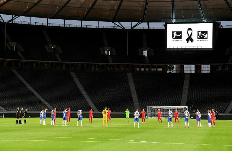Empty feeling: Players hold a minute's silence ahead of the game at the Olympic Stadium