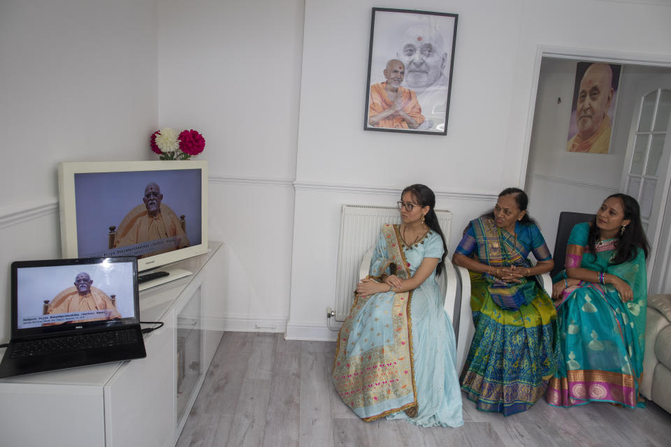 """Aagna Patel, 16, Pushpa Patel, 68, Hemali Patel 42, dressed in their best saris, watch Guru Pujya Swayamprakashdas speak to them through their television screen in the comfort of their living room in their suburban home in Hemel Hempstead, England, on Sunday, June 14, 2020. """"That is what we would have worn to the temple,"""" said Hemali, """"so it felt only right to dress for the occasion."""" (AP Photo/Elizabeth Dalziel)"""