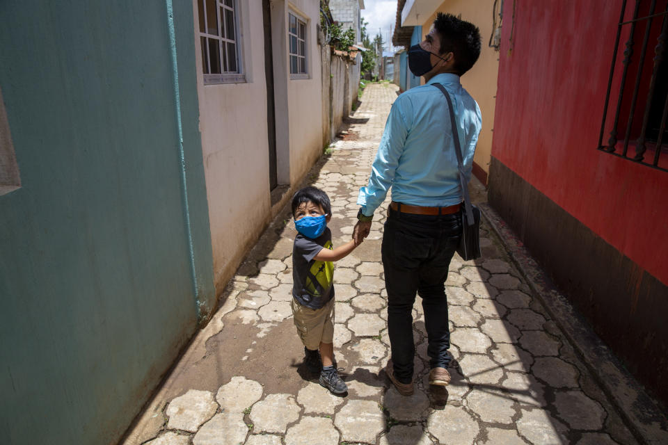 Teacher Gerardo Ixcoy and his three-year-old son Dylan greet a neighbor as Ixcoy arrives home after a day of giving individual instruction to his sixth-grade students, in Santa Cruz del Quiche, Guatemala, Wednesday, July 15, 2020. By afternoon Ixcoy pedals his classroom-on-a-trike for home to beat a mandatory curfew set in place to help curb the spread of the new coronavirus. (AP Photo/Moises Castillo)