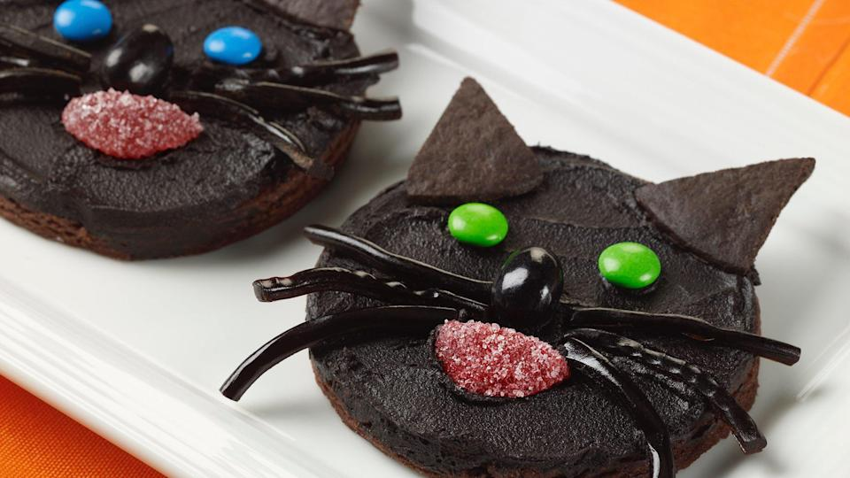 """<p>Black cat owners are going to be excited about this recipe. Forget <a href=""""https://www.thedailymeal.com/eat/chocolate-chip-cookies-ranked-gallery?referrer=yahoo&category=beauty_food&include_utm=1&utm_medium=referral&utm_source=yahoo&utm_campaign=feed"""" rel=""""nofollow noopener"""" target=""""_blank"""" data-ylk=""""slk:chocolate chip cookies"""" class=""""link rapid-noclick-resp"""">chocolate chip cookies</a> — serve this black cat cookie recipe at your Halloween gathering. This chocolate-based cookie is covered in rich chocolate frosting and decorated with assorted candies.</p> <p><a href=""""https://www.thedailymeal.com/recipe/black-cat-cookies-halloween?referrer=yahoo&category=beauty_food&include_utm=1&utm_medium=referral&utm_source=yahoo&utm_campaign=feed"""" rel=""""nofollow noopener"""" target=""""_blank"""" data-ylk=""""slk:For the Black Cat Cookies recipe, click here"""" class=""""link rapid-noclick-resp"""">For the Black Cat Cookies recipe, click here</a>.</p>"""
