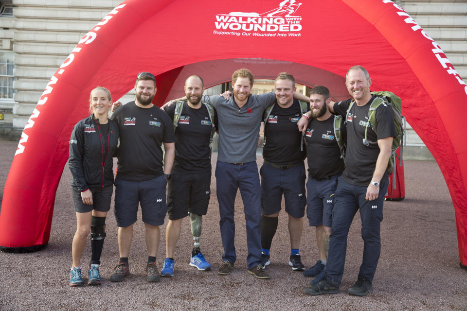 LONDON, UNITED KINGDOM - NOVEMBER 1: Prince Harry poses with Kirsty Ennis, Andrew Bement, Matt Fisher, Alec Robotham, Scott Ransley and Stewart Hill as he meets with members of the Walking With The Wounded team in the forecourt of Buckingham Palace after their latest endeavour, the Walk Of Britain on November 1, 2015 in London, England. Six members of the Walk of Britain team concluded their 1000-mile trek, which began on 22 August in Scotland and continued through the length and breadth of the country to London. (Photo by Heathcliff O'Malley-WPA Pool / Getty Images)