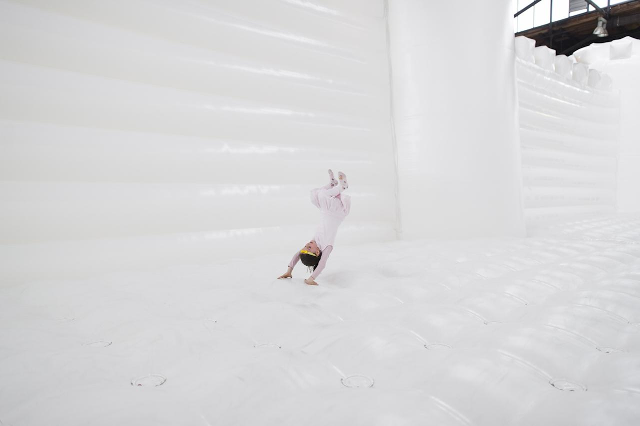 """BERLIN, GERMANY - JUNE 27: A child jump in the """"White Bouncy Castle"""" of installation artist William Forsythe on June 27, 2013 in Berlin, Germany. The work is a giant, inflatable white castle that Forsythe says encourages people to dance the moment they step into it. """"White Bouncy Castle"""" will be open to visitors at Lokhalle Schoeneberg until July 14 and is part of the """"Foreign Affairs"""" series of Berliner Festspiele. (Photo by Timur Emek/Getty Images)"""