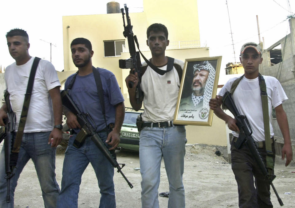 """FILE - In this July 31, 200 file photo, Palestinian Zakaria Zubeidi, then leader of the Al-Aqsa Martyrs' Brigades militant group in the West Bank town of Jenin, holds a picture of Yasser Arafat, as he poses with other militants after they set the town's Governorate on fire overnight. For nearly two decades, Zubeidi has been an object of fascination for Israelis and Palestinians alike, who have seen his progression from a child actor to a swaggering militant, to the scarred face of a West Bank theater promoting """"cultural resistance"""" to Israeli occupation. In his latest act, he has emerged as one of Israel's most wanted fugitives after tunneling out of a high-security prison on Monday, Sept. 6, 2021 with five other Palestinian militants. (AP Photo/Mohammed Ballas, File)"""