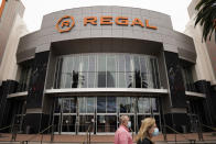 FILE - Two shoppers walk past a Regal movie theater in Irvine, Calif., on Sept. 8, 2020. Indoor movie theaters are open in most states, except New Mexico and Washington D.C., although some are on a county-by-county basis. Regal theaters are currently closed in the U.S, and independent cinemas vary by location, but AMC Theaters (the nation's biggest chain) and Cinemark are largely up and running. Approximately 54% of screens are open in the U.S., according to the National Association of Theater Owners. (AP Photo/Jae C. Hong, File)