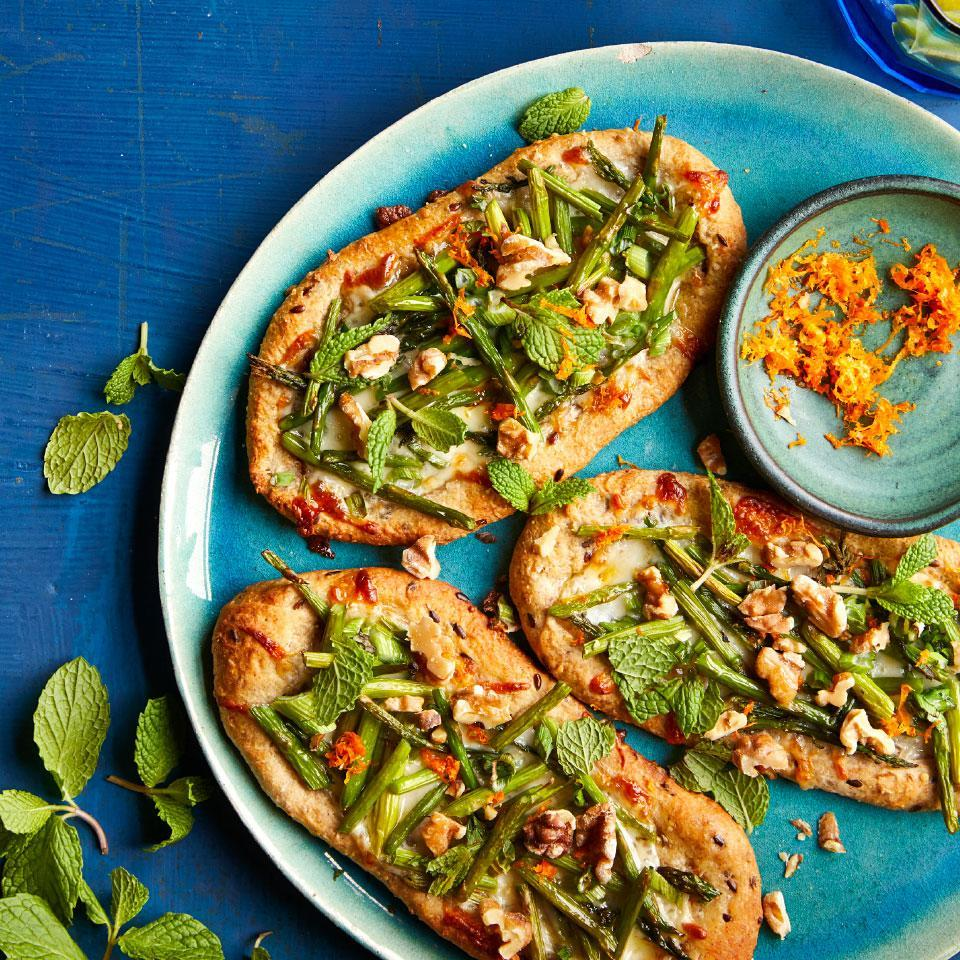 "<p>These cute mini pizzas are topped with asparagus, walnuts, mint, orange and smoked mozzarella cheese for what may sound like a crazy combination of pizza toppings, but try it for yourself. The mix puts a downright delicious spin on pizza night. <a href=""http://www.eatingwell.com/recipe/270477/asparagus-smoked-mozzarella-pizzettes/"" rel=""nofollow noopener"" target=""_blank"" data-ylk=""slk:View recipe"" class=""link rapid-noclick-resp""> View recipe </a></p>"
