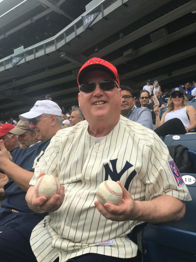 In this photo provided by Brian Giorgis, Marist womens basketball coach Brian Giorgis shows the two foul balls he caught at a game between the Cleveland Indians and the New York Yankees on Saturday, May 5, 2018, at Yankee Stadium, in New York. A longtime baseball fan, Giorgis says hed never come close to getting a foul ball until he caught two in consecutive innings. (Courtesy of Brian Giorgis via AP)