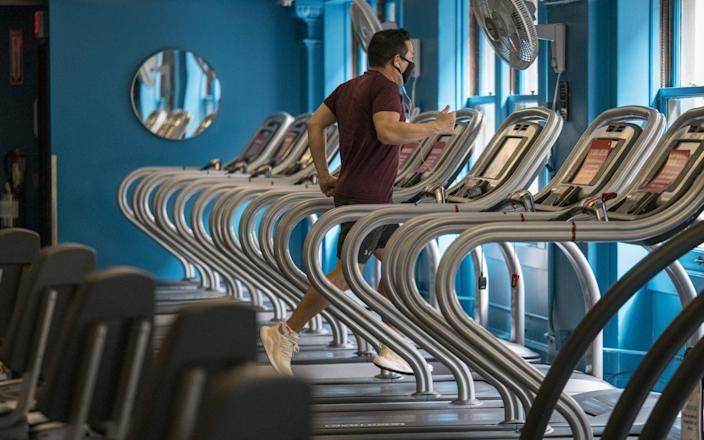 A person wearing a protective mask exercises at a Crunch Fitness gym location in San Francisco, California, U.S., on Thursday, Sept. 17, 2020. - David Paul Morris/Bloomberg