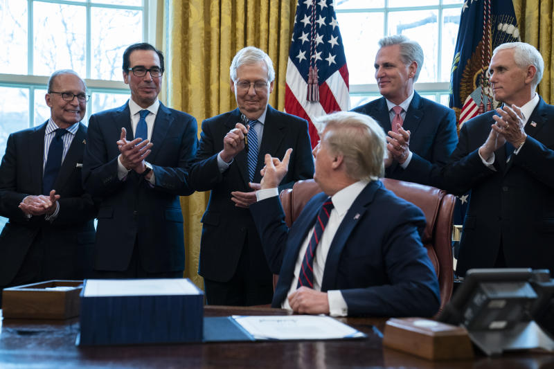 President Donald Trump hands a pen to Senate Majority Leader Mitch McConnell of Ky., after signing the coronavirus stimulus relief package in the Oval Office at the White House, Friday, March 27, 2020, in Washington. From left, White House chief economic adviser Larry Kudlow, Treasury Secretary Steven Mnuchin, McConnell, Trump, House Minority Leader Kevin McCarty, R-Calif., and Vice President Mike Pence. (AP Photo/Evan Vucci)