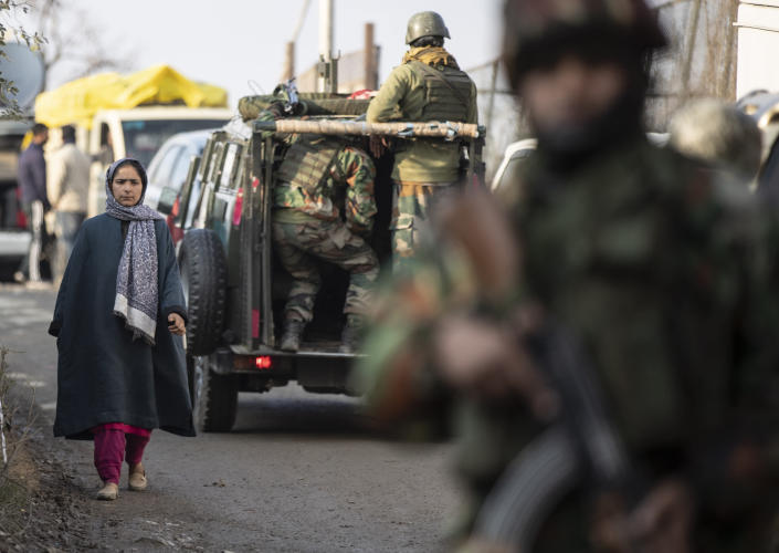 A Kashmiri woman walks past security officers keeping guard near the site of an attack on the outskirts of Srinagar, Indian controlled Kashmir, Thursday, Nov. 26, 2020. Anti-India rebels in Indian-controlled Kashmir Thursday killed two soldiers in an attack in the disputed region's main city, the Indian army said.(AP Photo/Mukhtar Khan)