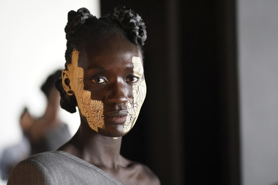 A model appears backstage in preparation for the Thom Browne fashion show during New York Fashion Week at The Shed, on Saturday, Sept. 11, 2021, in New York. (Photo by Charles Sykes/Invision/AP)