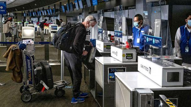 PHOTO: A traveler wearing a protective mask checks in at the United Airlines check-in counter at San Francisco International Airport in San Francisco, Dec. 21, 2020.  (David Paul Morris/Bloomberg via Getty Images, FILE)
