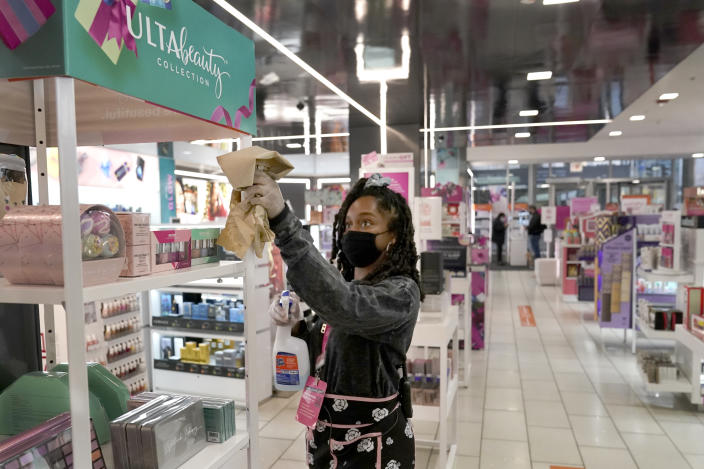 Tamia Prescott sanitizes a cosmetic display Thursday, Nov. 19, 2020, at an Ulta beauty store on Chicago's Magnificent Mile. (AP Photo/Charles Rex Arbogast)