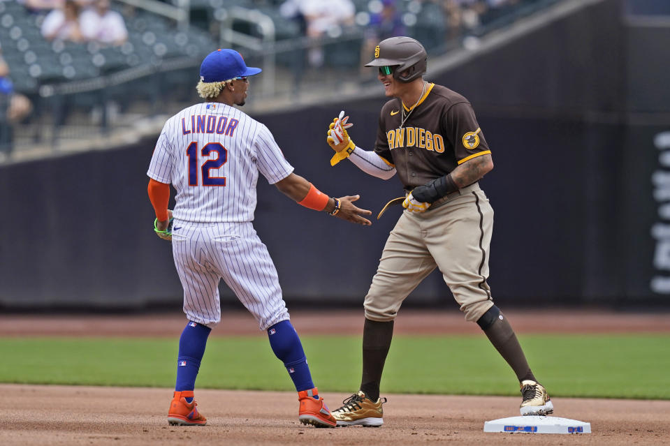San Diego Padres' Manny Machado, right, and New York Mets shortstop Francisco Lindor tease one another during the first inning of a baseball game at Citi Field, Sunday, June 13, 2021, in New York. (AP Photo/Seth Wenig)