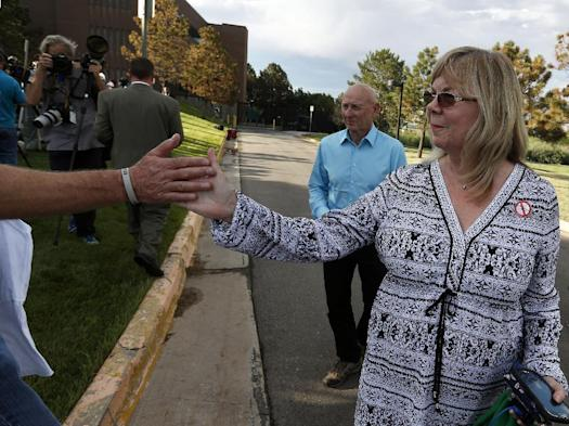 Sandy Phillips, right, and her husband, Lonnie, who lost their daughter Jessica Ghawi in the 2012 Aurora movie theater massacre, gives a high-five to Tom Teves, who lost his son Alex in the attack, after attending the reading of the verdict in the trial of shooter James Holmes at the Arapahoe County District Court in Centennial, Colo., Thursday, July 16, 2015. (Photo: AP Photo/Brennan Linsley)