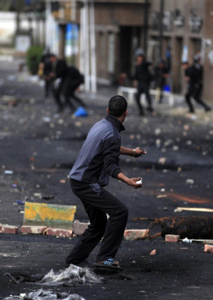 An Egyptian protester throws stones at riot police during clashes near a state security building in Port Said, Egypt, Thursday, March 7, 2013. Clashes between protesters and police continued into a fifth day on Thursday in the restive Egyptian city of Port Said. (AP Photo/Khalil Hamra)