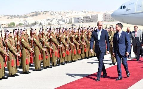 "As the Duke of Cambridge embarked on his landmark tour to the Middle East, due to become the first member of the British Royal family to undertake an official visit to Israel, he could be forgiven for feeling the weight of history on his shoulders. As befits the president of the Football Association though, he also had one other thing on his mind: watching the World Cup. The Duke, who has landed in Amman, Jordan for the first day of his tour, asked his new friend Crown Prince Hussein bin Abdullah II to record the England match for him, making those around him promise not to tell him the score. The Duke and the Prince, 23, planned to watch the recorded game after dinner, as the Jordanian Royal family hosted their visitor. Speaking to the media before he had a chance to switch on the television, the Duke joked of the England-Panama match: ""On pain of death, please don't tell me the score."" Jordan is the first stop on Prince William's tour of the Middle East Credit: Tim Rooke/REX/Shutterstock The plans for football appeared to be the start of a firm friendship between the two royals, as the Prince drove the Duke around Amman in person for their first day of engagements. As the Duke stepped off his RAF Voyager into the 32C heat of Amman, he was greeted warmly by Crown Prince Hussein for the visit he is said to be ""very much looking forward to"". The Prince then drove him to FabLab, one of his own initiatives to equip young people with technology skills. In a visit clearly designed to impress the Duke, he was invited to start up a laser cutter which swiftly produced the crest of Aston Villa, the team he supports, on a wooden shield. ""That's familiar,"" he said with a smile when he spotted the Villa crest on the machine. ""Very good. You have done your research."" He was also given a model of the gas tank on one of his beloved Ducati motorbikes bearing the Villa crest. He shares a passion for motorbikes with Crown Prince Hussein, a Sandhurst-trained second lieutenant in the Jordanian army. The Duke is to spend five days Jordan, Israel and the Palestinian territories at the request of the Government. The Duchess of Cambridge has not accompanied her husband on the trip at home with Prince George, Princess Charlotte and Prince Louis. A Kensington Palace spokesman said: ""The historic nature of this tour is of course important and the duke considers it a great privilege to be undertaking the first ever official royal tour of Israel and the Occupied Palestinian Territories and to be able to help further strengthen the friendship between Jordan and the United Kingdom."""