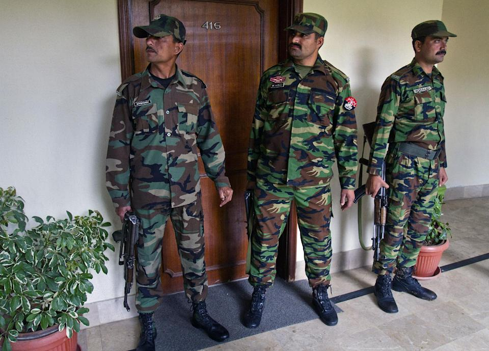 Pakistani police officers stand guard outside the room of Mir Hazar Khan Khoso, not pictured, nominated for Pakistan's caretaker prime minister, in Islamabad, Pakistan, Sunday, March 24, 2013. Pakistan's election commission has chosen a former high court chief justice Khoso nominated by the country's outgoing ruling party to serves as caretaker prime minister in the run up to a historic national election this spring. (AP Photo/Anjum Naveed)