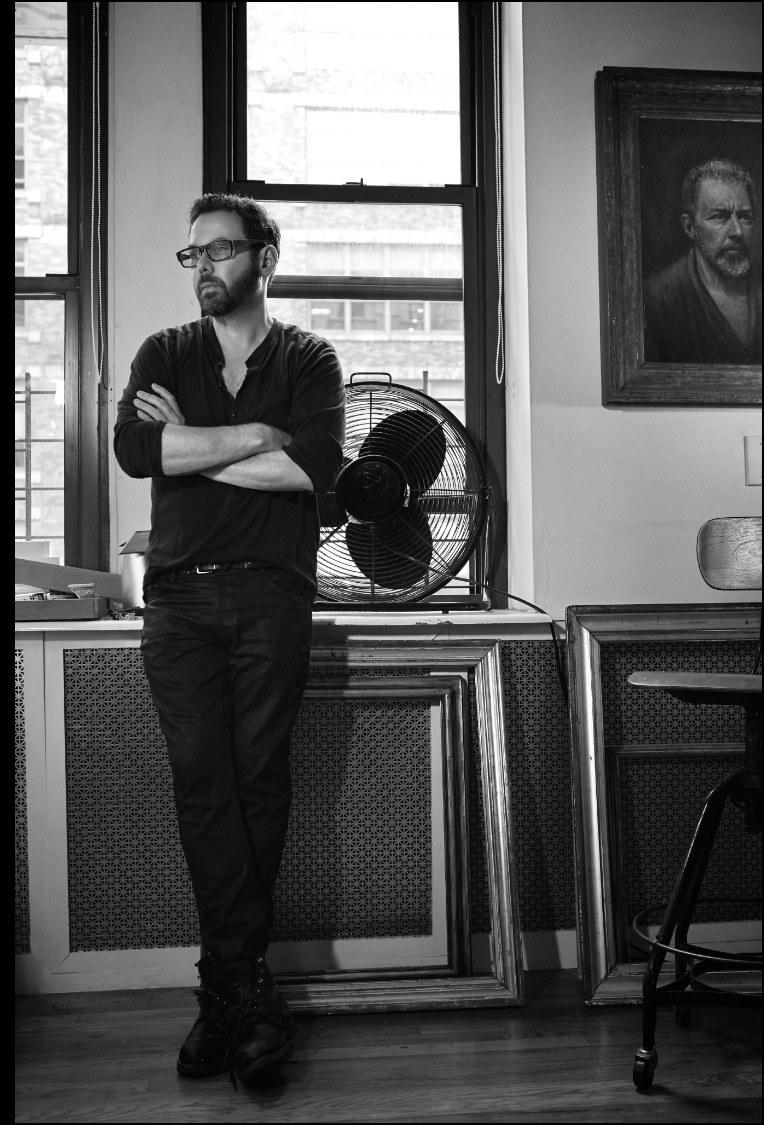 Neil Grayson in his New York studio, standing next to a portrait he painted of his father in 1987.