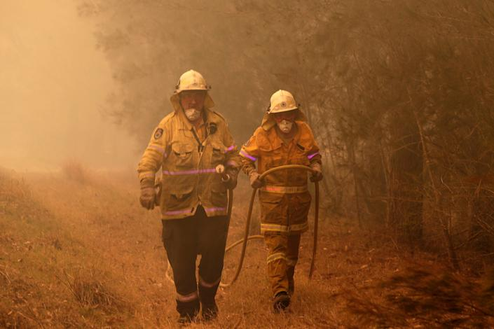 New South Wales firefighters drag their water hose after putting out a spot fire on the state's south coast. (Photo: ASSOCIATED PRESS)