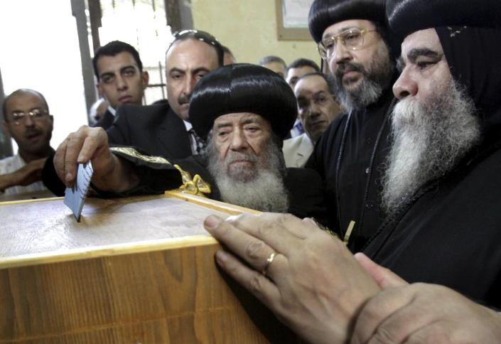 """<span class=""""caption"""">Egypt's Coptic Pope Shenouda III, center, casts his vote for Parliament elections in Cairo, Egypt in November 2010.</span> <span class=""""attribution""""><a class=""""link rapid-noclick-resp"""" href=""""https://www.apimages.com/metadata/Index/Mideast-Egypt-Elections/afc5bd975a584d11ab414c02faa54817/11/0"""" rel=""""nofollow noopener"""" target=""""_blank"""" data-ylk=""""slk:AP Photo"""">AP Photo</a></span>"""