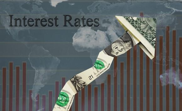 """Interest Rates"" written above a bar chart trending upwards, with a dollar bill forming the line and arrow."