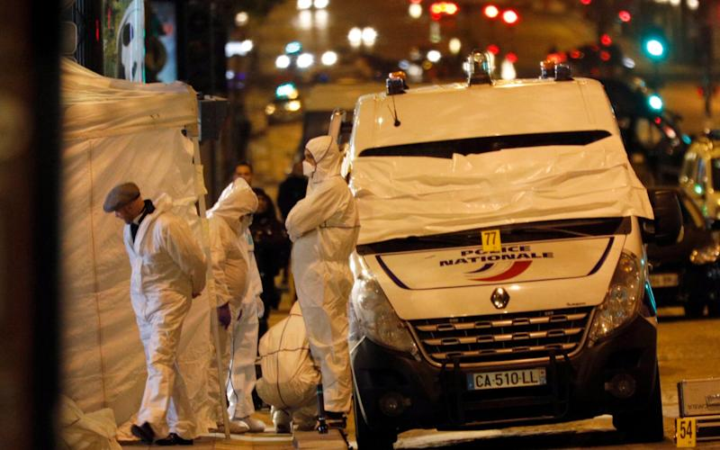 Forensic experts investigate the crime scene after a fatal shooting in which a police officer was killed along with an attacker on the Champs Elysees avenue in Paris, France, Friday, April 21, 2017 - Credit: AP