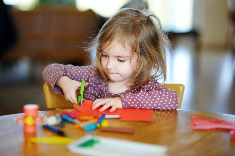 Small girl playing with art supplies at nursery