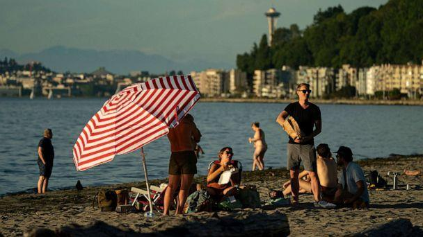 PHOTO: People take in the evening at Alki Beach in Seattle, June 24, 2021. An intense heat wave is set to pummel the Pacific Northwest, potentially setting records in Seattle, Portland and the interior. (Ruth Fremson/The New York Times via Redux)