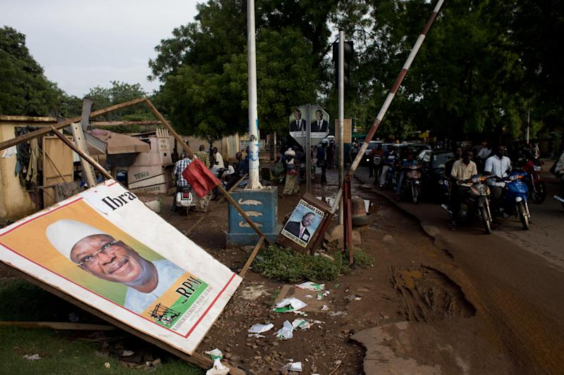 Campaign posters still line a route, as Malians waited for results from last Sunday's presidential elections, in Bamako, Mali, Thursday, Aug. 1, 2013. Results were expected Friday. (AP Photo/Rebecca Blackwell)