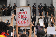 Demonstrators hold up signs during a protest in front of Los Angeles City Hall, Tuesday, June 2, 2020, in Los Angeles over the death of George Floyd. Floyd died in police custody on Memorial Day in Minneapolis. (AP Photo/Mark J. Terrill)
