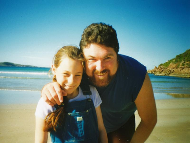 An eight-year-old Sarah Frazer wearing dungarees pictured with her smiling father Peter at a beach.
