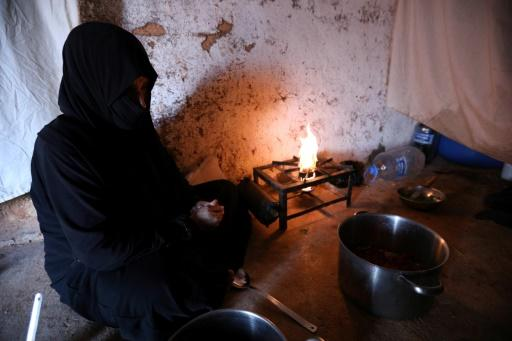 Umm Samer, a displaced woman from Eastern Ghouta, prepares an iftar meal at their home in Maaret Masrin, Idlib province on May 26, 2018