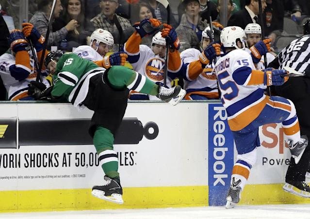 Dallas Stars' Sergei Gonchar (55), of Russia, stops himself from falling into the visitors bench after a collision with New York Islanders' Cal Clutterbuck (15) in the second period of an NHL hockey game, Sunday, Jan. 12, 2014, in Dallas. (AP Photo/Tony Gutierrez)