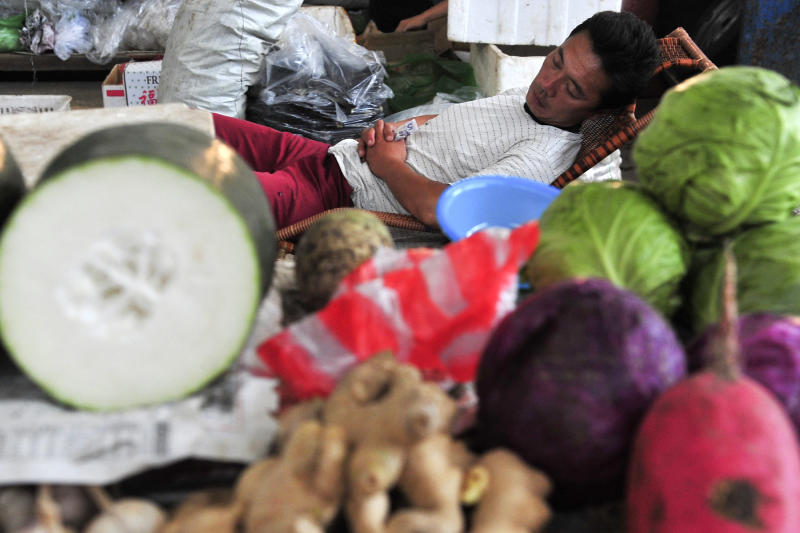 A vegetable vendor holds a banknote while napping at a market in Shenyang, in northeast China's Liaoning province Tuesday July 31, 2012. Chinese leaders have warned that economic growth could slow further and are calling for renewed efforts to boost domestic demand. (AP Photo)  CHINA OUT