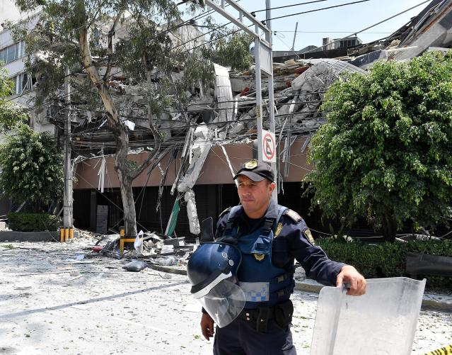<p>A police officer stands guard near a building which collapsed after a queke rattled Mexico City on September 19, 2017.<br> A powerful earthquake shook Mexico City on Tuesday, causing panic among the megalopolis' 20 million inhabitants on the 32nd anniversary of a devastating 1985 quake. The US Geological Survey put the quake's magnitude at 7.1 while Mexico's Seismological Institute said it measured 6.8 on its scale. The institute said the quake's epicenter was seven kilometers west of Chiautla de Tapia, in the neighboring state of Puebla.<br> (Photo: Omar Torres/AFP/Getty Images) </p>