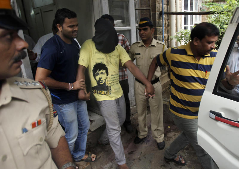 Police officials escort an accused, with the head covered with black cloth, in the gang rape of a photojournalist after producing him before a court in Mumbai, India, Sunday, Aug. 25, 2013. Police on Sunday arrested the last of five men wanted in the gang rape of a 22-year-old Indian woman in Mumbai, and said charges would be filed soon in a case that has incensed the public and fueled debate over whether women can be safe in India.(AP Photo/Rafiq Maqbool)