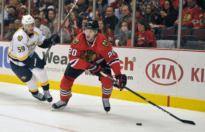 Nashville Predators' Roman Josi (59) defends as the Chicago Blackhawks' Brandon Saad (20) looks to pass during the second period of an NHL hockey game on Friday, April 19, 2013, in Chicago. (AP Photo/Jim Prisching)